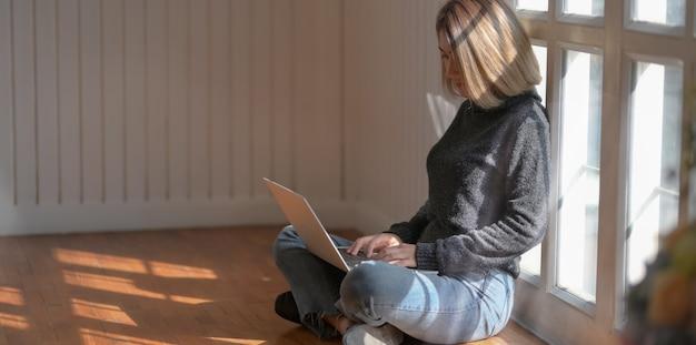 Jeune pigiste travaillant sur son projet assise près des fenêtres