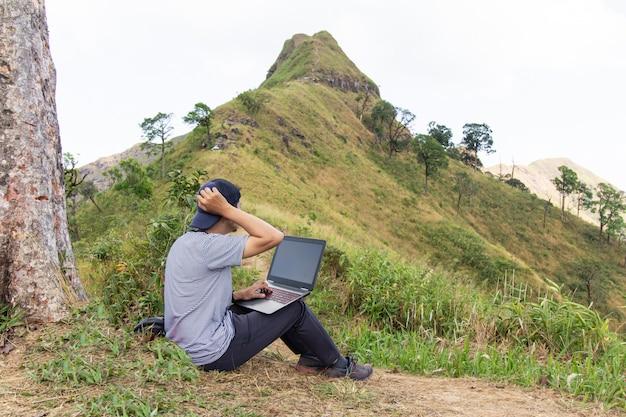 Jeune pigiste travaille sur un ordinateur portable à l'extérieur