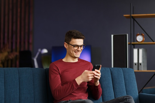 Jeune pigiste utilisant un smartphone et souriant. homme heureux utilisant des applications de téléphonie mobile, sms, navigation sur internet, regardant un smartphone, assis à la maison. les jeunes travaillant avec des appareils mobiles.
