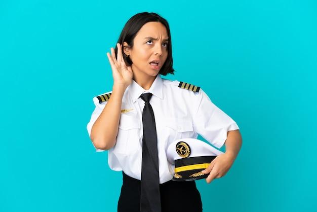 Jeune pilote d'avion sur fond bleu isolé écoutant quelque chose en mettant la main sur l'oreille