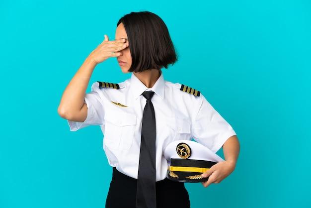 Jeune pilote d'avion sur fond bleu isolé faisant un geste d'arrêt et couvrant le visage