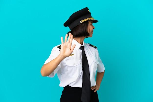 Jeune pilote d'avion sur fond bleu isolé faisant un geste d'arrêt et déçu