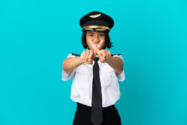 Jeune pilote d'avion sur fond bleu isolé faisant un geste d'arrêt avec sa main pour arrêter un acte