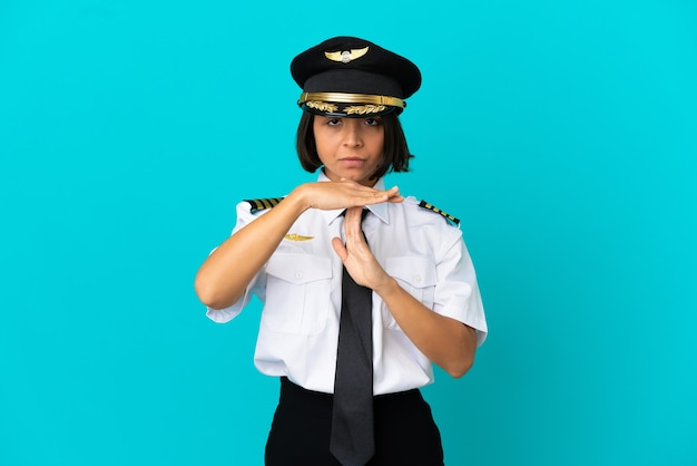 Jeune pilote d'avion sur fond bleu isolé faisant un geste de temps mort