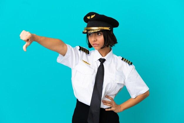 Jeune pilote d'avion sur fond bleu isolé montrant le pouce vers le bas avec une expression négative