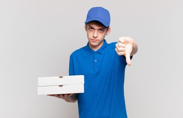Jeune pizza livre garçon se sentant fâché, en colère, agacé, déçu ou mécontent, montrant les pouces vers le bas avec un regard sérieux