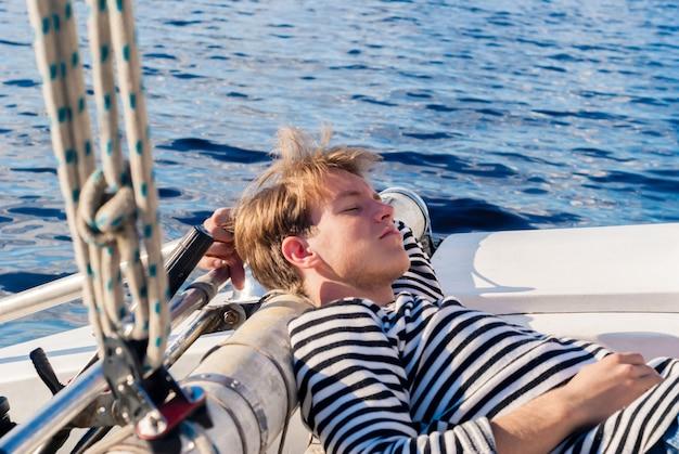 Jeune plaisancier faisant la sieste à l'arrière du yacht pendant l'inactivité forcée par temps calme