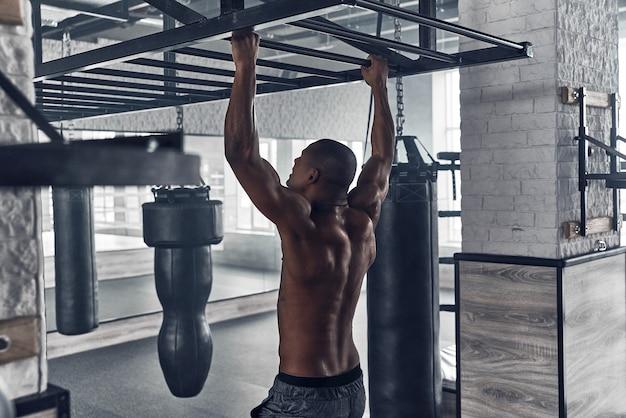 Jeune et plein d'énergie. jeune homme africain torse nu faisant des tractions tout en faisant de l'exercice dans la salle de sport