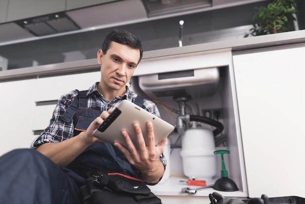Jeune plombier est assis près de l'évier avec tablette.