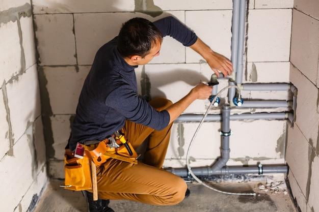 Le jeune plombier masculin fait le câblage des canalisations d'égout