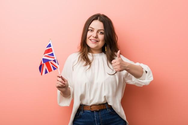 Jeune, plus, femme bien roulée, tenue, drapeau, royaume-uni, sourire, et, levée pouce, haut