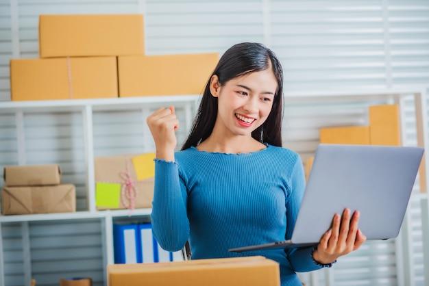 Jeune pme entreprise propriétaire démarrage heureux main tenant un ordinateur portable.