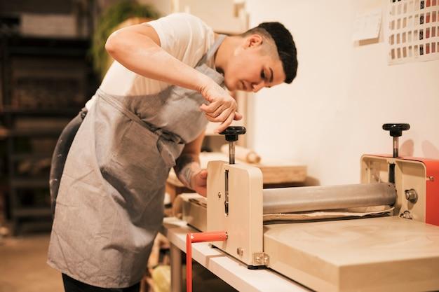 Jeune potière ajustant la machine dans son atelier