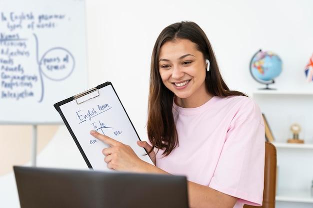 Jeune professeur d'anglais faisant son cours en ligne