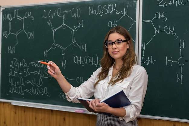 Un jeune professeur de chimie au tableau noir explique et montre par pointeur un nouveau sujet