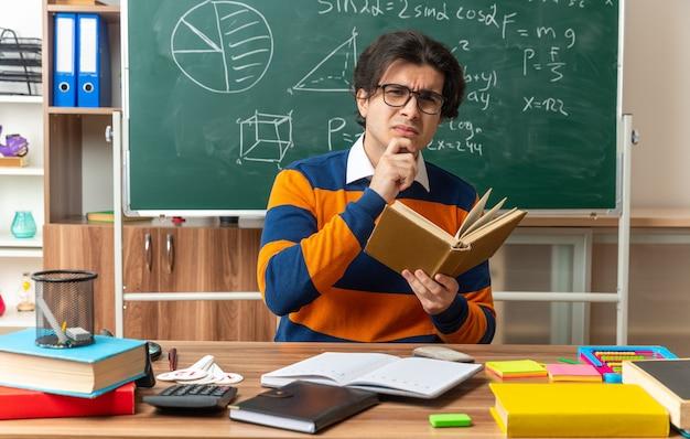 Jeune professeur de géométrie caucasien confus portant des lunettes assis au bureau avec des fournitures scolaires en classe tenant un livre en gardant la main sur le menton regardant à l'avant