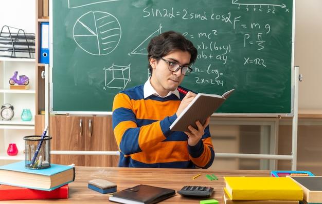 Jeune professeur de géométrie concentré portant des lunettes assis au bureau avec des fournitures scolaires en classe écrivant sur un bloc-notes avec un stylo