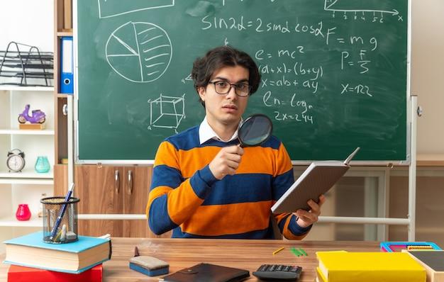 Jeune professeur de géométrie impressionné portant des lunettes assis au bureau avec des fournitures scolaires en classe tenant un bloc-notes et une loupe regardant à l'avant