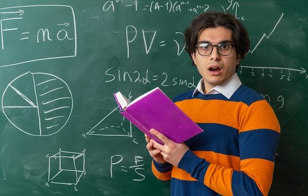 Jeune professeur de géométrie impressionné portant des lunettes debout dans la vue de profil devant le tableau en classe tenant un livre ouvert regardant à l'avant