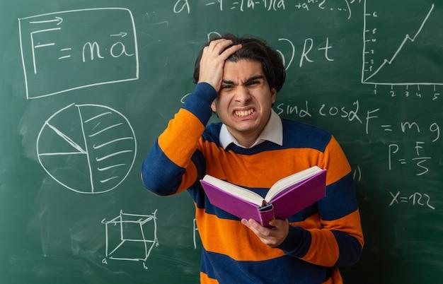 Jeune professeur de géométrie irrité debout devant le tableau en classe tenant un livre regardant l'avant en gardant la main sur la tête