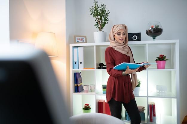Jeune professeur. jeune enseignant portant un foulard se sentant impliqué dans la préparation de la leçon