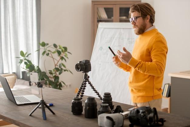 Jeune professeur de photographie professionnelle montrant un nouveau modèle de photocaméra à ses étudiants en ligne et expliquant ses fonctionnalités