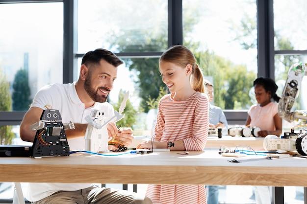 Jeune professeur de robotique assis à la table avec son élève