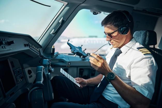 Un jeune professionnel masculin avec des gadgets est assis aux commandes dans le cockpit et se prépare à décoller