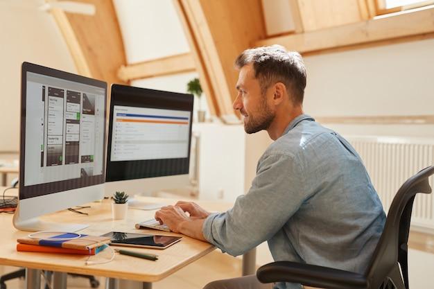 Jeune programmeur assis à la table en tapant sur le clavier de l'ordinateur et en regardant le moniteur de l'ordinateur il travaille au bureau