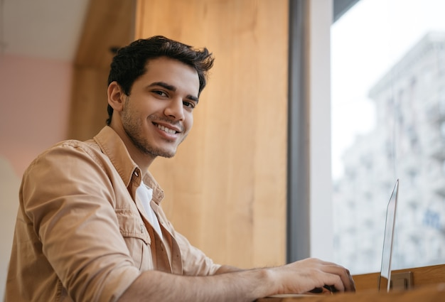 Jeune programmeur indien à l'aide d'un ordinateur portable travaillant à domicile