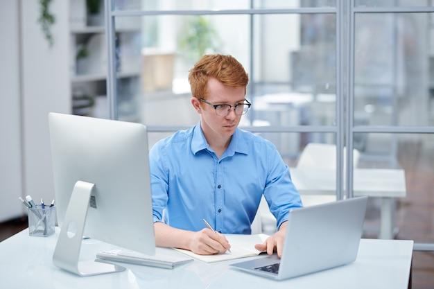 Jeune programmeur à la recherche de logiciels sur l'écran de l'ordinateur portable et prendre des notes tout en étant assis par un bureau