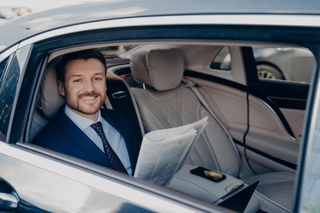 Jeune propriétaire d'entreprise souriant indépendant en costume formel bleu, assis à l'arrière d'une limousine, lisant le journal, heureux de lire de bonnes nouvelles écrites sur lui-même, prenant le volant à l'arrière de la voiture