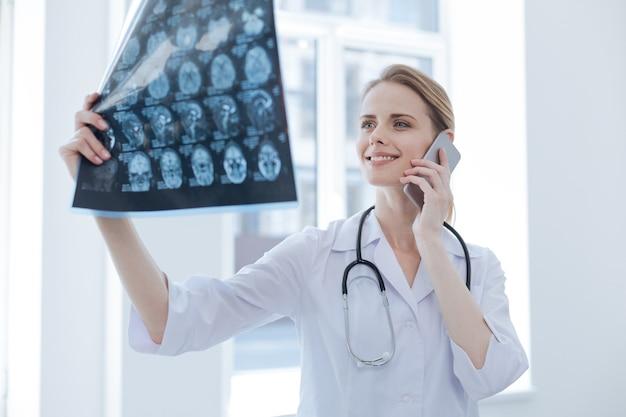 Un jeune radiologue dynamique et optimiste travaillant à l'armoire à rayons x tout en examinant les rayons x du cerveau et en utilisant un smartphone