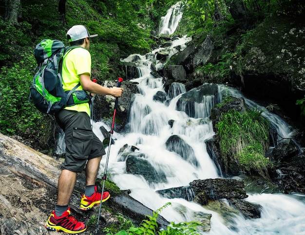 Jeune randonneur actif avec sac à dos et bâtons de randonnée regardant la cascade dans la forêt