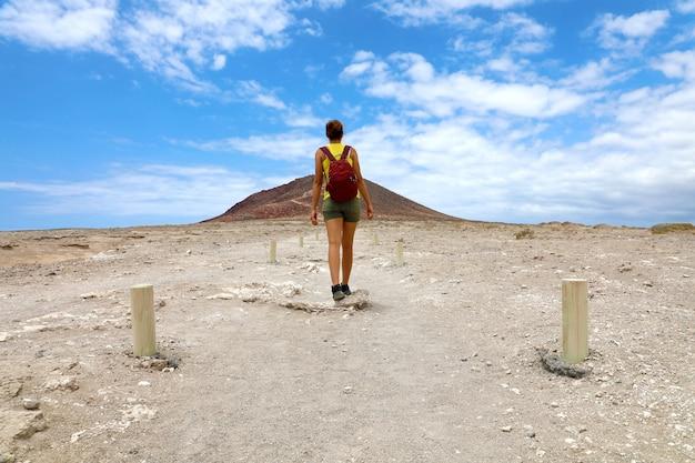 Jeune randonneur femme marchant dans le chemin de la montagne rouge à tenerife