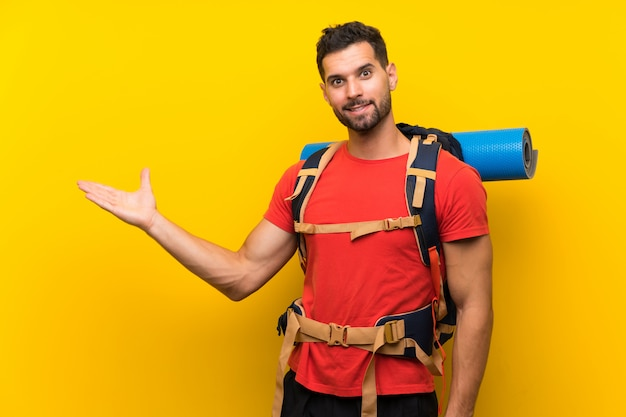 Jeune randonneur homme tenant une surface imaginaire sur la paume