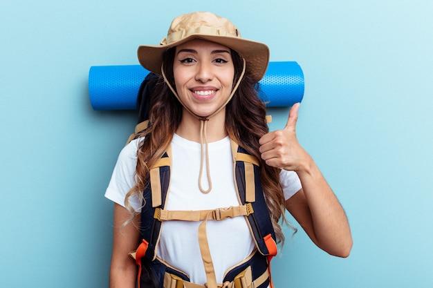Jeune randonneur mixed race woman isolé sur fond bleu souriant et levant le pouce vers le haut