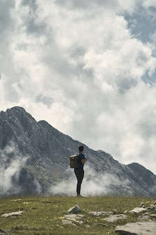 Jeune randonneur avec un sac à dos entouré de montagnes sous un ciel nuageux en cantabrie, espagne