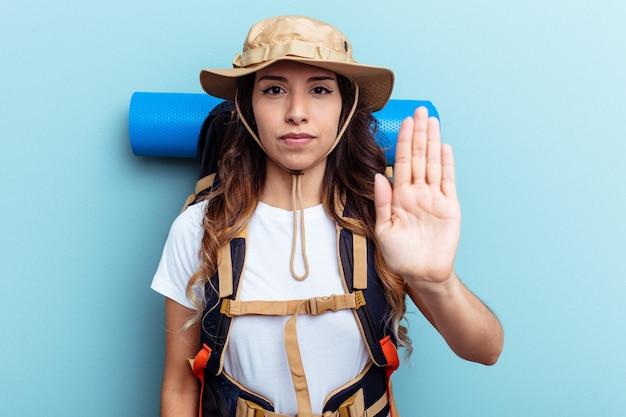 Jeune randonneuse métisse femme isolée sur fond bleu debout avec la main tendue montrant un panneau d'arrêt, vous empêchant.