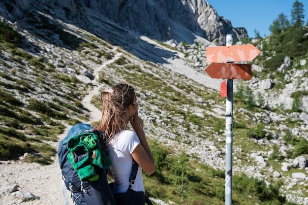 Jeune randonneuse avec un sac à dos envisageant de se tenir debout près d'un panneau au milieu d'un sentier de randonnée en montagne.