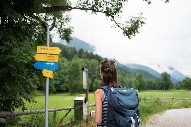 Jeune randonneuse avec un sac à dos en regardant un panneau indiquant la direction à prendre.