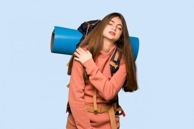 Jeune randonneuse souffrant de douleurs à l'épaule pour avoir fait un effort sur le bleu