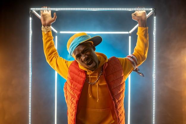 Jeune rappeur élégant pose dans un cube lumineux. artiste de hip-hop, chanteur de rap, spectacle de break-dance, mode de vie de divertissement