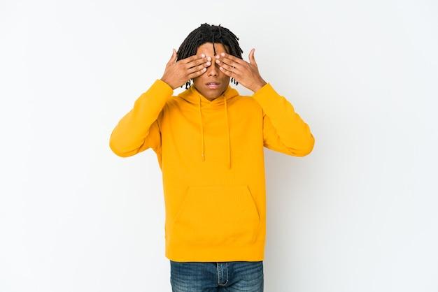 Jeune rastaman afro-américain peur couvrant les yeux avec les mains.