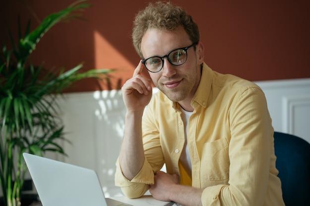 Jeune rédacteur pigiste beau utilisant un ordinateur portable travaillant en ligne à domicile