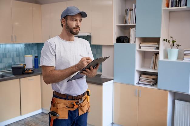 Jeune réparateur caucasien écrivant dans le cahier