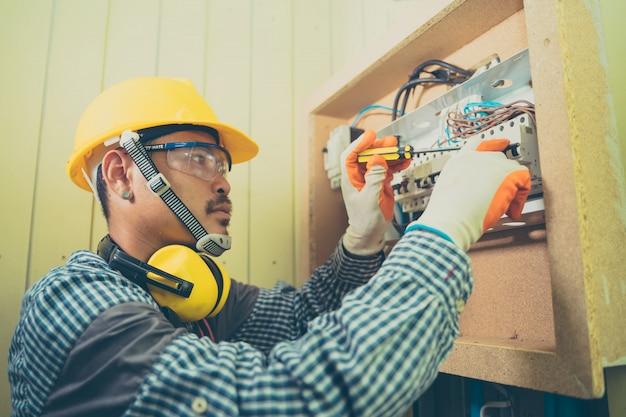Jeune réparateur fixant l'électricité, l'électricien vérifiant les fils dans une boîte électrique avec une pince dans le couloir d'un système électrique résidentiel.