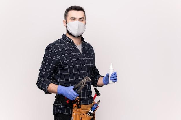 Jeune réparateur en masque de protection et gants pour réparer des meubles ou du matériel de plomberie
