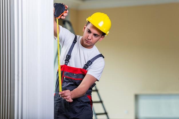 Jeune réparateur avec un ruban à mesurer travaillant sur des réparations