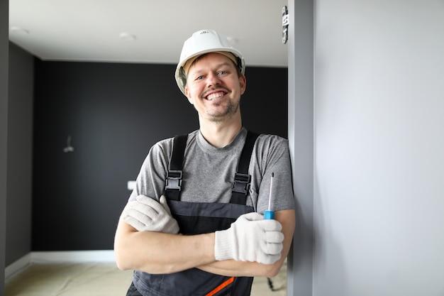 Jeune réparateur souriant debout dans un appartement vide et tenant un tournevis dans les mains
